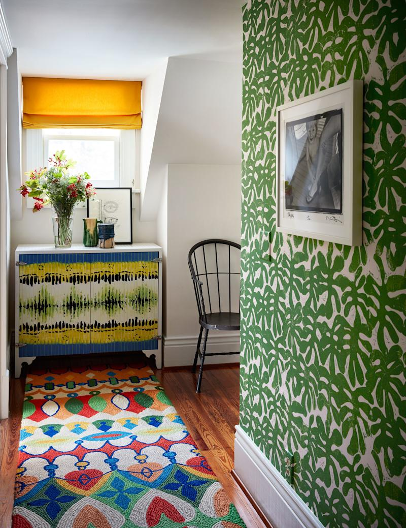 A vibrant rug lines a corridor. Custom cabinet by RP Miller painted by Monica Mahoney; Paper Mills wall covering