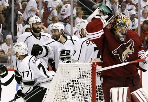 As Phoenix Coyotes goalie Mike Smith, far right, sprays water on his neck, Los Angeles Kings' Drew Doughty (8) celebrates with Rob Scuderi (7), Dustin Penner (25) and Jeff Carter (77) after a goal by Carter in the second period during Game 2 of the NHL hockey Stanley Cup Western Conference finals, Tuesday, May 15, 2012, in Glendale, Ariz. (AP Photo/Ross D. Franklin)