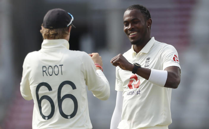 England's Jofra Archer, right, celebrates with captain Joe Root the dismissal of Pakistan's Mohammad Abbas during the second day of the first cricket Test match between England and Pakistan at Old Trafford in Manchester, England, Thursday, Aug. 6, 2020. (Lee Smith/Pool via AP)