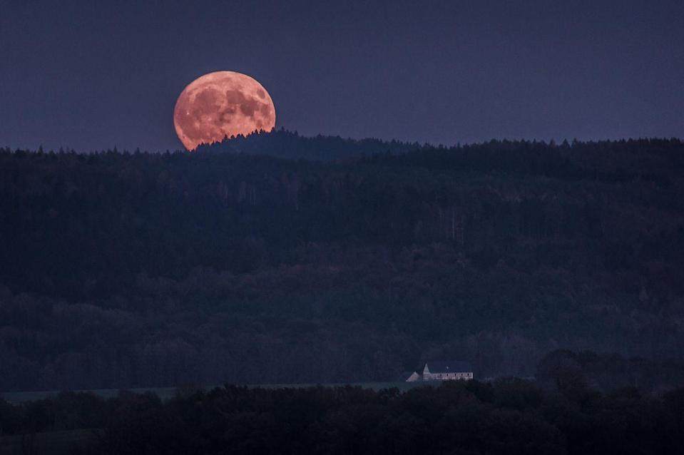 <p>A full moon tucks behind the Koenigshainer Berge mountains in Koenigshain, Germany // November 03, 2017</p>