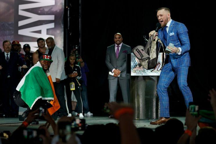 Floyd Mayweather (L) poses with the Irish flag while Conor McGregor rifles through Mayweather's backpack. (Getty)
