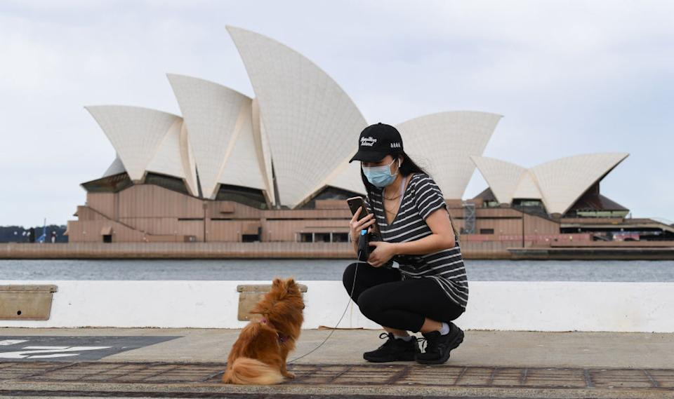 A woman wearing a face mask takes a photo of her dog with the Opera House in the background in Sydney, Australia.