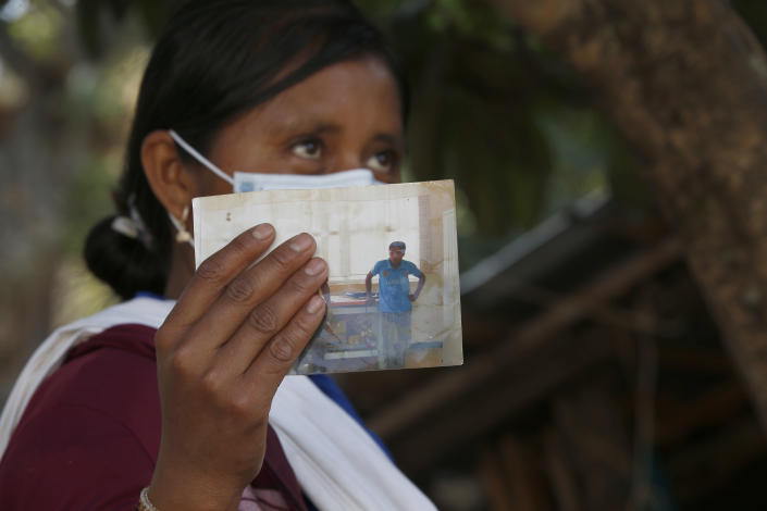 Basilia Tepetitlan holds a photo of her husband who was murdered along with nine other musicians including a 15-year-old boy by a criminal gang that burned them and sent their vehicles off a cliff in Alcozacan, Guerrero state, Mexico, Thursday, April 29, 2021. The community got scholarships for the victims' orphaned children and homes for the widows like Tepetitlan. (AP Photo/Marco Ugarte)