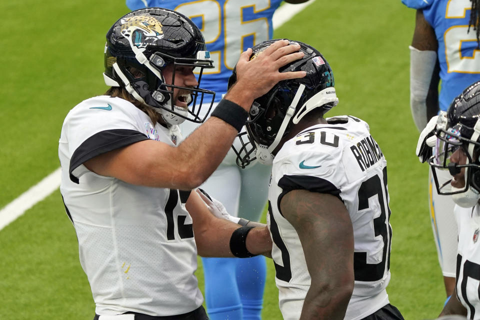 Jacksonville Jaguars running back James Robinson, right, celebrates with Gardner Minshew after lunging into the end zone for a touchdown during the first half of an NFL football game against the Los Angeles Chargers Sunday, Oct. 25, 2020, in Inglewood, Calif. (AP Photo/Alex Gallardo )
