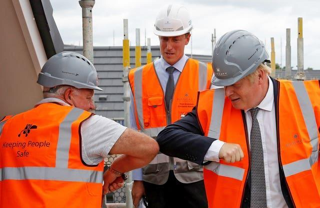 Prime Minister Boris Johnson greets a worker with an elbow bump during a visit to a construction site in Cheshire (Phil Noble/PA)