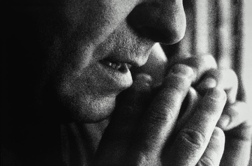 Man using telephone, covering mouthpiece with hand, (grainy B&W)