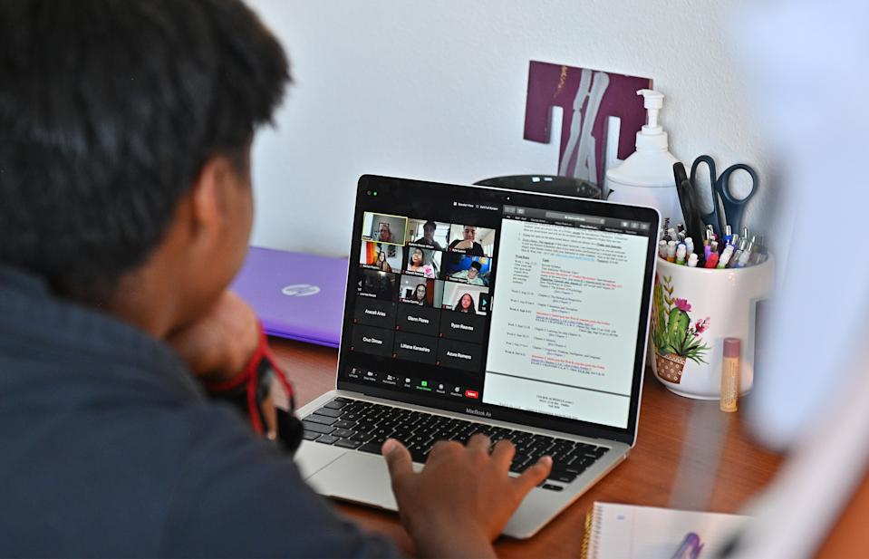 ALBUQUERQUE, NEW MEXICO - AUGUST 17:  Kyalynn Moore-Wilson, a freshman, sits at a desk in her dorm room as she participates in a Zoom meeting for an 'Introduction to Psychology' course as classes begin amid the coronavirus (COVID-19) pandemic on the first day of the fall 2020 semester at the University of New Mexico on August 17, 2020 in Albuquerque, New Mexico. The course will meet in person four times during the fall semester with the remaining classes and coursework completed online. To help prevent the spread of COVID-19, the university has moved to a hybrid instruction model that includes a mixture of in-person and remote classes. According to the school, about 70 percent of classes are being taught online.  (Photo by Sam Wasson/Getty Images)