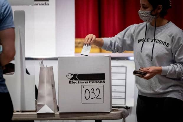 A voter, seen in this image taken from the door of a polling station, casts a ballot in Toronto's University-Rosedale riding on Sept. 20, 2021.  (Evan Mitsui/CBC - image credit)