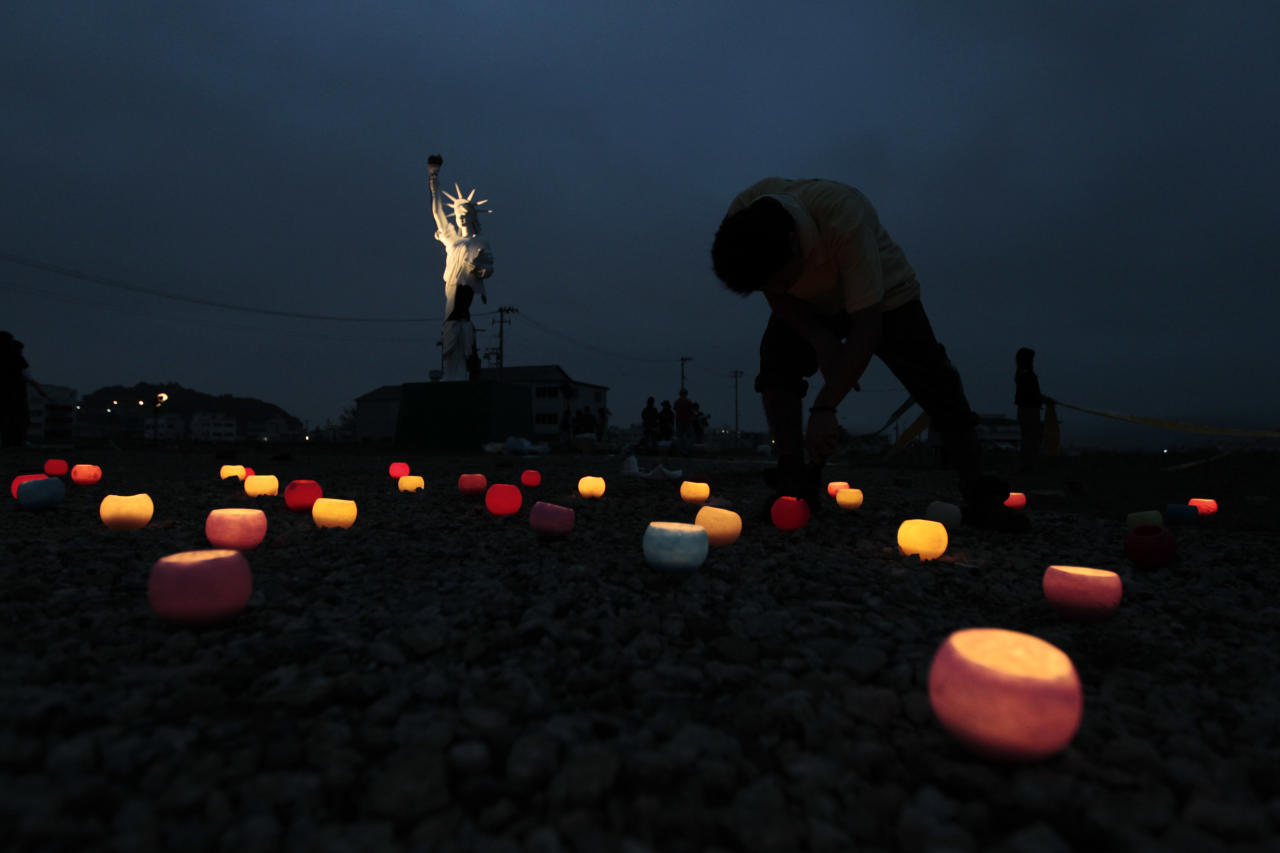 A volunteer lights a candle by a damaged replica of the Statue of Liberty during an event to pay tribute to victims of both the Sept. 11 terrorist attacks and the March 11 earthquake in Ishinomaki, northeastern Japan, Sunday, Sept. 11, 2011.   As the world commemorated the 10th anniversary of the World Trade Center attacks, Sunday was doubly significant for Japan. It marked six months since the massive earthquake and tsunami on March 11, a date now seared in the national consciousness. (AP Photo/Hiro Komae)