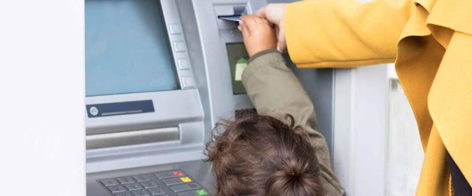 Mother and daughter standing at cash machine, putting in card
