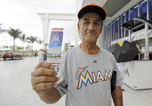Cuban American Luis Azcuy, of Hialeah, Fla., stands outside of Marlins Park with his tickets before a baseball game between the Miami Marlins and Houston Astros, Friday, April 13, 2012, in Miami. Azcuy is a season ticket holder, but was offended by remarks made by manager Ozzie Guillen in which he expressed admiration for Cuban leader Fidel Castro. Azcuy is in support of Guillen losing his job. Guillen was suspended for five games. (AP Photo/Lynne Sladky)