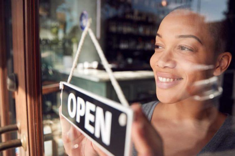 Female Owner Of Start Up Coffee Shop Or Restaurant Turning Round Open Sign On Door