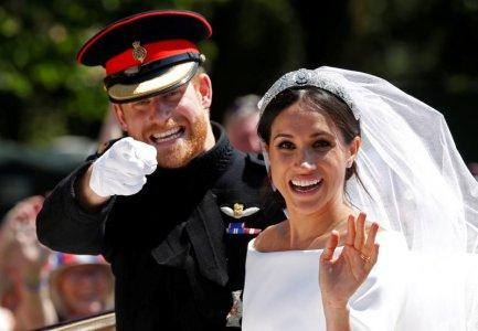 FILE PHOTO: Britain's Prince Harry gestures next to his wife Meghan as they ride a horse-drawn carriage after their wedding ceremony at St George's Chapel in Windsor Castle in Windsor, Britain, May 19, 2018. REUTERS/Damir Sagolj