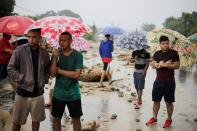 Residents hold umbrellas as they observe a bridge affected by rains from Storm Eta, in Toyos