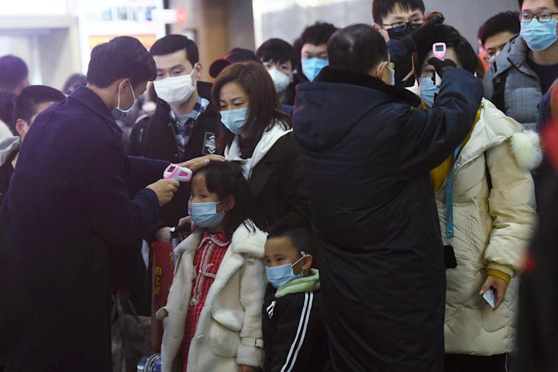 Staff members check body temperatures of the passengers arriving from the train from Wuhan to Hangzhou, at Hangzhou Railway Station ahead of the Chinese Lunar New Year in Zhejiang