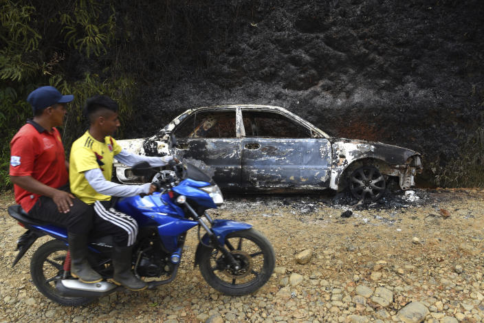 Men ride past a vehicle incinerated during a skirmish between illegal armed groups in which at least five people were killed in Jamundi, southwest Colombia, Friday, Jan. 17, 2020. Authorities say rebels with the former Revolutionary Armed Forces of Colombia operate in the area and may have been involved. (AP Photo/Christian EscobarMora)