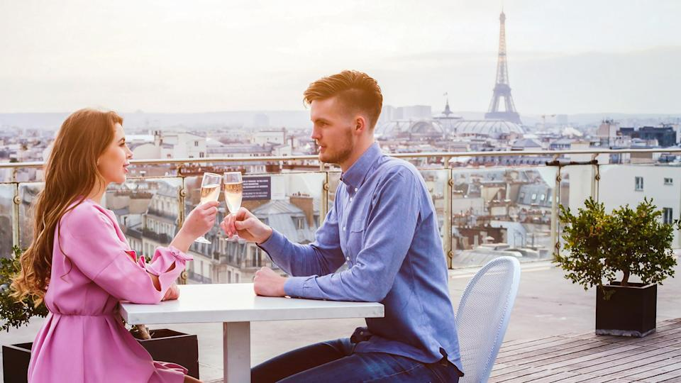 How Much to Tip When Traveling to These 25 Countries, couple drinking champagne in luxury rooftop restaurant in Paris