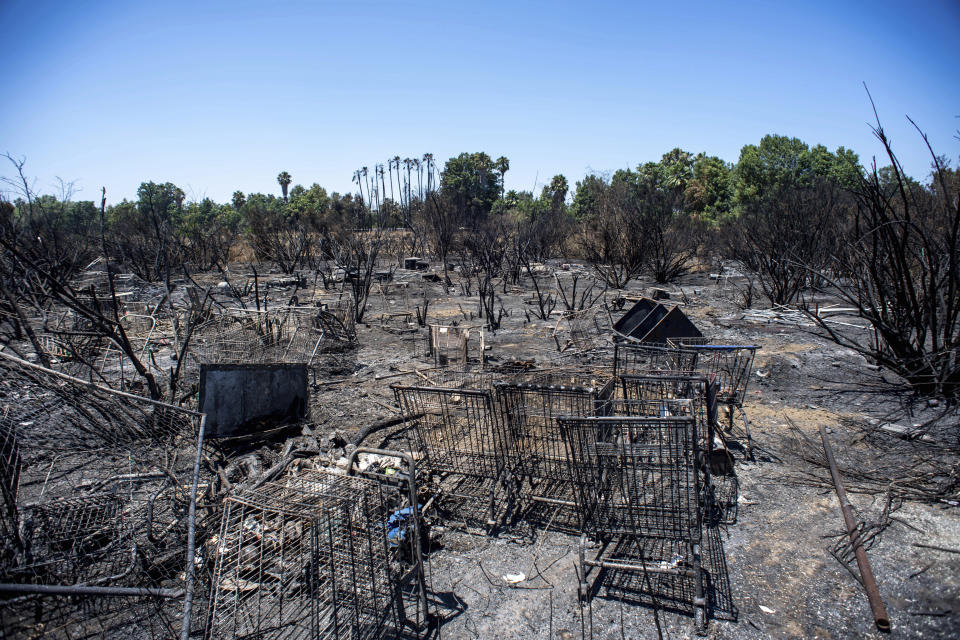 FILE - In this Wednesday, July 31, 2019, file photo, burned shopping carts are left behind after a fire in the Sepulveda Basin burned through brush and a homeless encampment in Van Nuys, Calif. Authorities say fires linked to homeless tents and camps are raising concern in Los Angeles, where they have claimed seven lives and caused tens of millions of dollars in damage to nearby businesses. The Los Angeles Times says the Fire Department handled 24 such fires a day in the first quarter of this year. (Sarah Reingewirtz/The Orange County Register via AP, File)