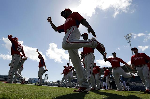 Philadelphia Phillies left fielder Zach Collier, center, warms up on the field before an exhibition baseball game against the Tampa Bay Rays, Monday, March 3, 2014, in Port Charlotte, Fla. (AP Photo/Steven Senne)