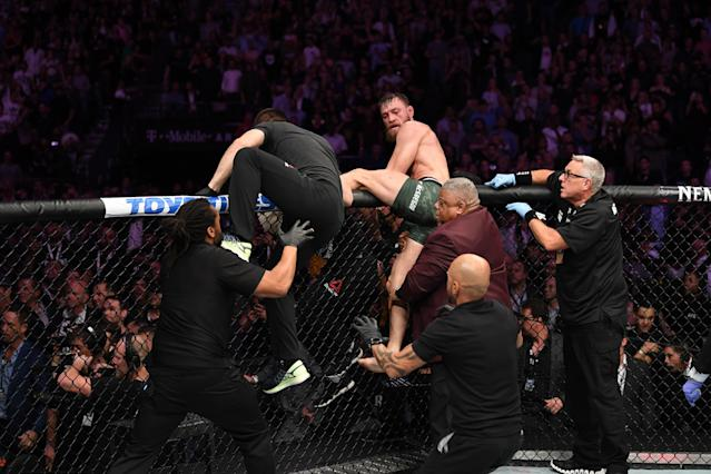 Conor McGregor attempts to leave the Octagon in chase of Khabib Nurmagomedov after their UFC lightweight championship bout at UFC 229 inside T-Mobile Arena on Saturday in Las Vegas. (Josh Hedges/Zuffa LLC)
