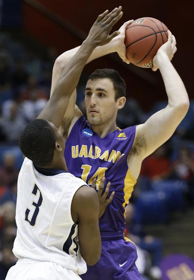 Albany forward Sam Rowley (14) is pressured by Mount St. Mary's guard Sam Prescott (3) in the first half of a first-round game of the NCAA college basketball tournament, Tuesday, March 18, 2014, in Dayton, Ohio. (AP Photo/Al Behrman)