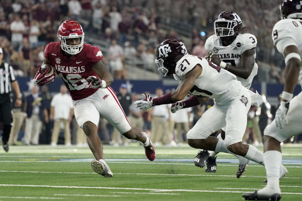 Arkansas wide receiver Treylon Burks (16) attempts to evade a tackle by Texas A&M defensive back Antonio Johnson (27), defensive lineman Tyree Johnson (3) and defensive back Leon O'Neal Jr. (9) in the second half of an NCAA college football game in Arlington, Texas, Saturday, Sept. 25, 2021. (AP Photo/Tony Gutierrez)