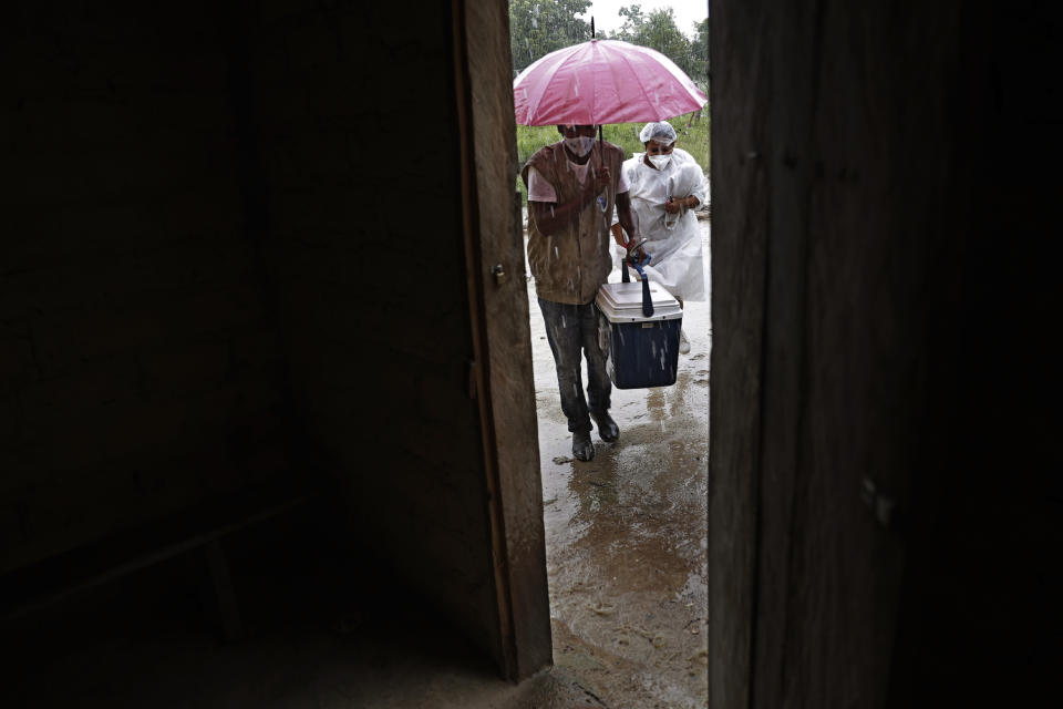 Health workers shield themselves with an umbrella as they arrive to administer Sinovac vaccines at a home in the Kalunga Vao de Almas community, a rural area on the outskirts of Cavalcante, Goias state, Brazil, Monday, March 15, 2021. The local government initiated its planned COVID-19 vaccination for priority Quilombolas populations with the goal of vaccinating 190 families residing in the Kalunga Vao de Almas, a community of Black people descended from slaves. (AP Photo/Eraldo Peres)