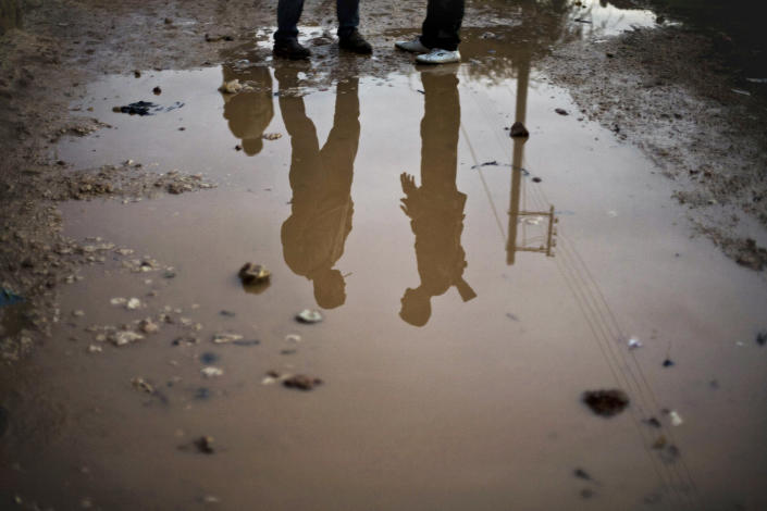 In this Wednesday, Dec. 12, 2012 photo, Free Syrian Army fighters are seen reflected in running water in the northern province of Aleppo, Syria. Syria's civil war has killed more than 40,000 people. (AP Photo/Manu Brabo)