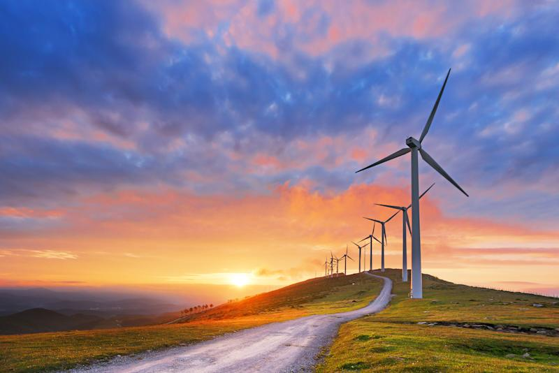 A road leading up to a row of wind turbines with the sun setting in the distance.