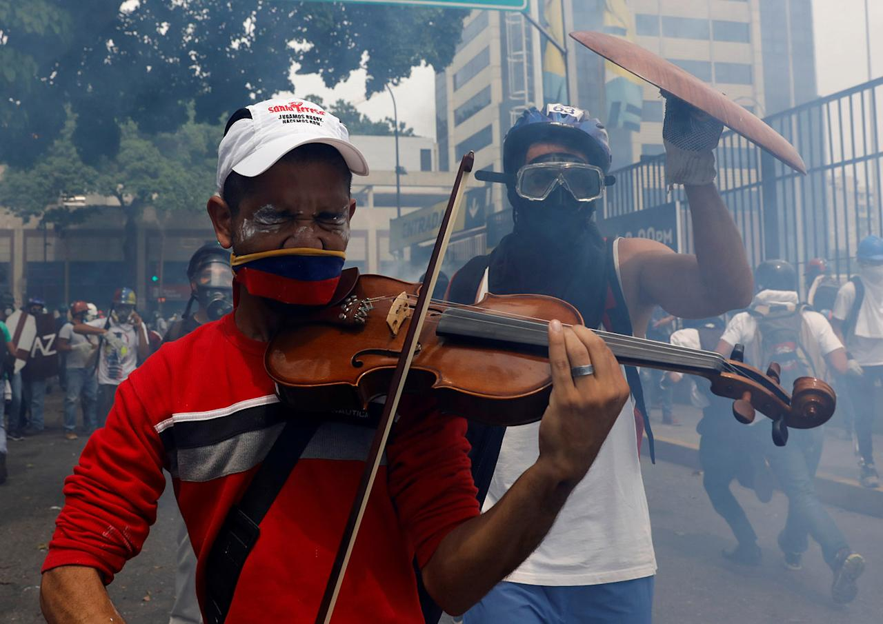 <p>An opposition supporter plays the violin during clashes with riot police, during a rally against President Nicolas Maduro in Caracas, Venezuela, May 8, 2017. (Photo: Carlos Garcia/Reuters) </p>