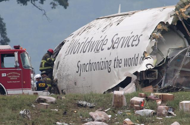 Investigators work near a section of debris of a UPS Airbus A300 cargo plane after it crashed on approach at Birmingham-Shuttlesworth International Airport this morning Wednesday Aug. 14, 2013 in Birmingham, Ala. The two pilots aboard the aircraft were killed. (AP Photo/Hal Yeager)