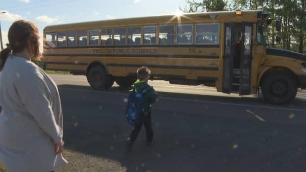 Mandy Acorn watches her son Harlan get on the bus to school. Earlier this week, a vehicle sped by the bus as it was stopped to let Harlan off after school. (Brian Higgins/CBC - image credit)
