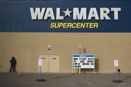 A man stands on a skateboard outside a Wal-Mart store in Williston