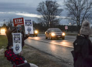Protesters stand across Prairieton Road from the Federal Death Chamber Friday, Dec. 11, 2020 in Terre Haute, Ind. The Trump administration plans to continue its unprecedented series of post-election federal executions Friday by putting to death Alfred Bourgeois who severely abused his 2-year-old daughter for weeks in 2002, then killed her by slamming her head against a truck's windows and dashboard.(Austen Leake/The Tribune-Star via AP)