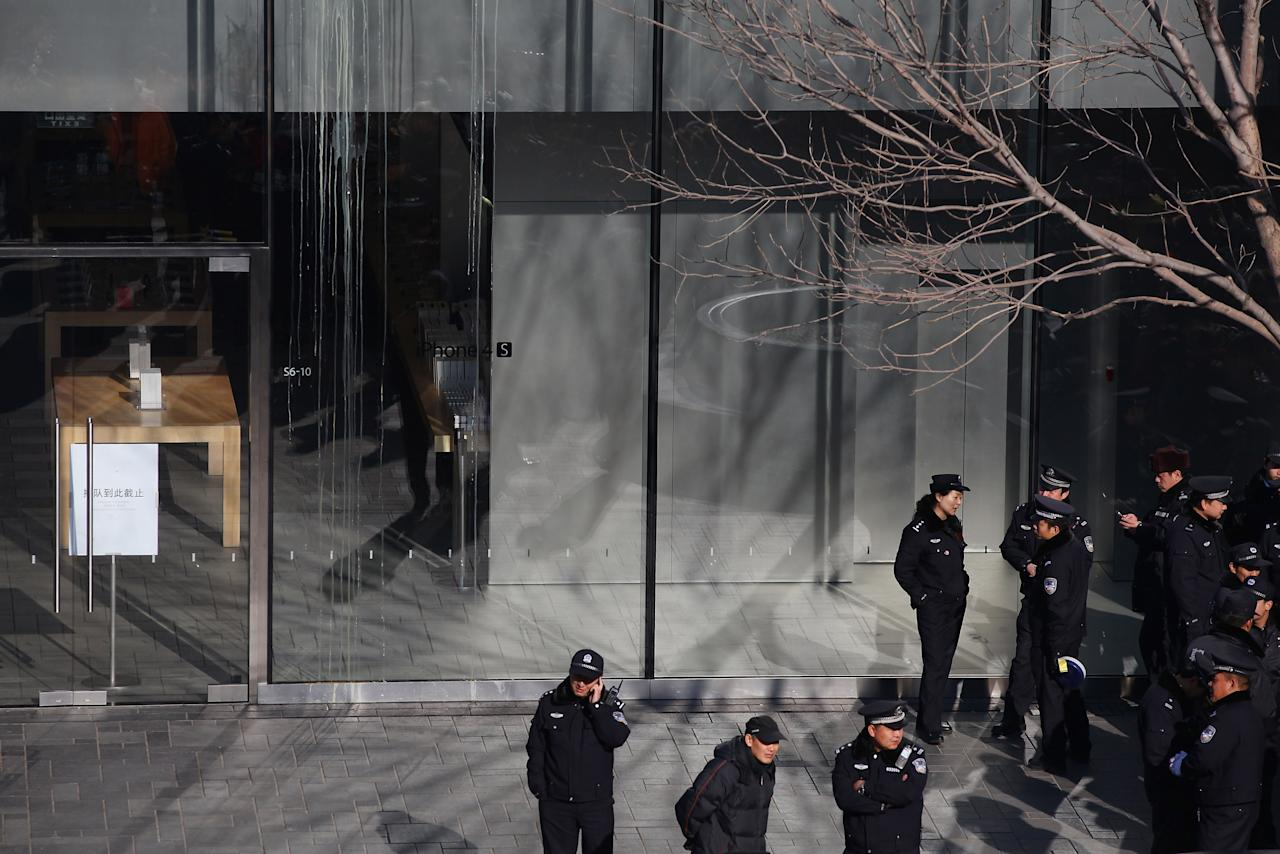 BEIJING, CHINA - JANUARY 13:   Police officers guard outside the Apple store beside the egg's stains on its glass wall on January 13, 2012 in Beijing, China. Chinese angry crowd shouted and threw eggs outside Apple's Beijing flagship store after it failed to open on schedule Friday to sell iPhone 4S.  (Photo by Feng Li/Getty Images)