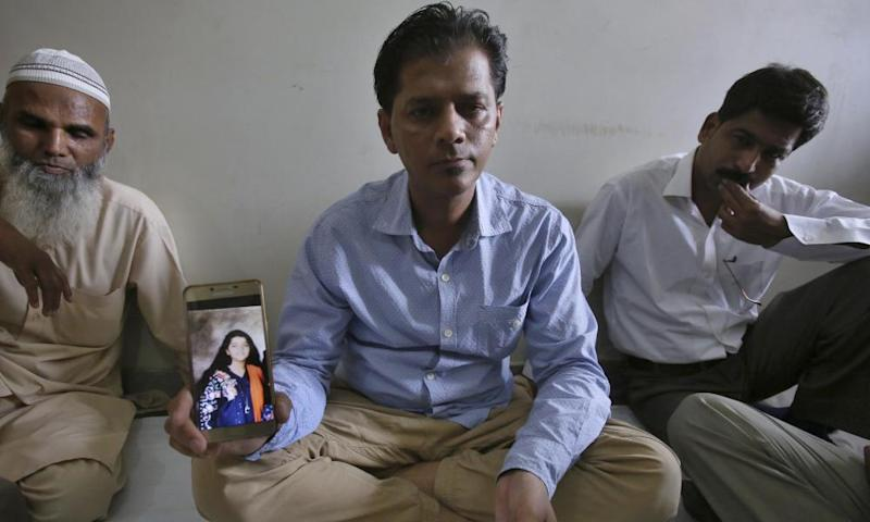 Abdul Aziz Sheikh, center, shows a picture of his daughter, Sabika Sheikh, who was killed in the May shooting at a Texas high school.