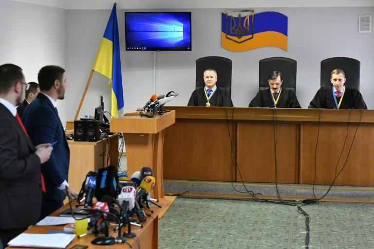 Lawyers (L) for ousted Ukrainian leader Viktor Yanukovych stand as a panel of three-judges begin to deliver the verdict of high treason against the former pro-Moscow president