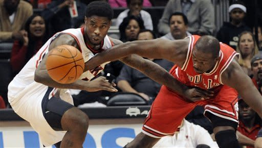 Atlanta Hawks forward Marvin Williams, left, battles for a loose ball with Chicago Bulls forward Luol Deng during the first half of an NBA basketball game, Saturday, Jan. 7, 2012, in Atlanta. (AP Photo/John Amis)