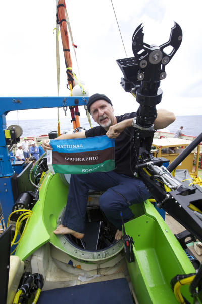 In a photo provided by National Geographic filmmaker and National Geographic Explorer-in-Residence James Cameron holds the National Geographic Society flag after he successfully completed the first ever solo dive to the Mariana Trench Monday March 26, 2012. The dive was part of Deepsea Challenge, a joint scientific expedition by Cameron, the National Geographic Society and Rolex to conduct deep-ocean research. (AP Photo/Mark Theissen, National Geographic)