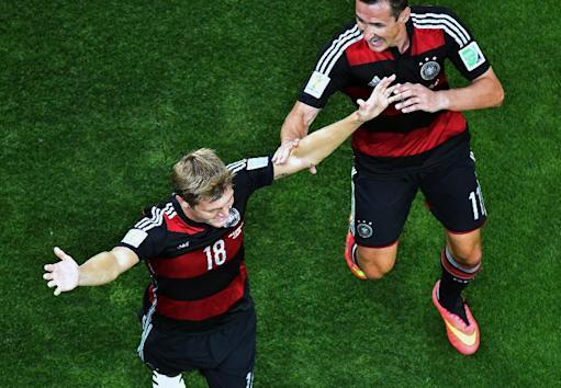 Germany's Toni Kroos, left, celebrates with Miroslav Klose after scoring during the World Cup semifinal soccer match between Brazil and Germany at the Mineirao Stadium in Belo Horizonte, Brazil, Tuesday, July 8, 2014. (AP Photo/Francois Xavier Marit, Pool)