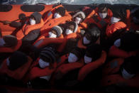 Migrants are rescued by aid workers of the Spanish NGO Open Arms, after fleeing Libya on board a precarious wooden boat in the Mediterranean sea, about 110 miles north of Libya, on Saturday, Jan. 2, 2021. (AP Photo/Joan Mateu)