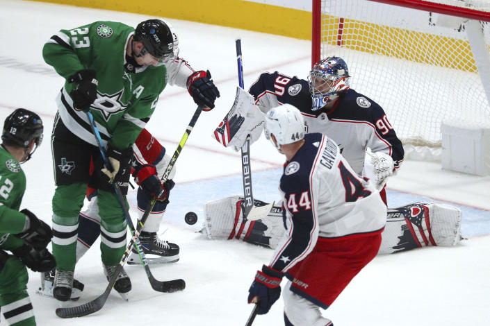 Dallas Stars defenseman Esa Lindell (23) tries to score on Columbus Blue Jackets goaltender Elvis Merzlikins (90) during the first period of an NHL hockey game Thursday, April 15, 2021, in Dallas. (AP Photo/Richard W. Rodriguez)