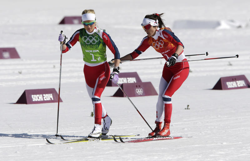Norway's Heidi Weng, right, changes to Norway's Therese Johaug during the women's 4x5K cross-country relay at the 2014 Winter Olympics, Saturday, Feb. 15, 2014, in Krasnaya Polyana, Russia. (AP Photo/Matthias Schrader)