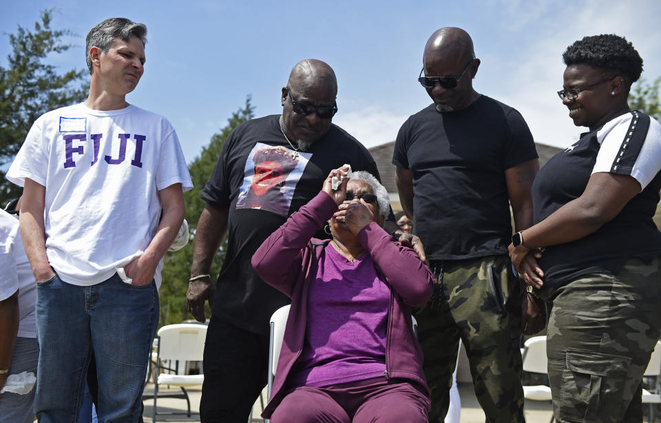 "Jessie Hamilton, seated, reacts as she is presented with a check to pay off her mortgage as LSU FIJI graduates gather to surprise their former house kitchen staff member, Saturday, April 3, 2021, and celebrate ""Jessie Hamilton Day"" in Baker, La. Behind her are, from left, FIJI graduate Andrew Fusaiotti, Hamilton's sons Andre' Hamilton and Craig Hamilton, and her granddaughter, Jamiah Hamilton. (Hilary Scheinuk/The Advocate via AP)"
