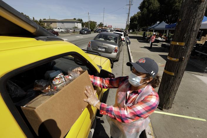 Rocio Bahena hands out boxes of food at Richmond High School, where 6,000 meals were distributed April 22. Bahena normally works as a food service aide in one of the elementary schools. Her husband was laid off and now she is the only provider for her family of four.