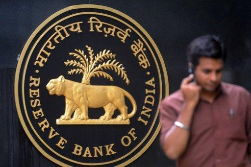 An Indian journalist speaks on a phone outside the head office of the Reserve Bank of India in Mumbai