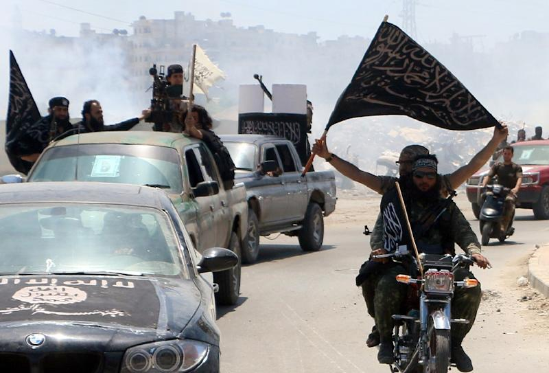 Fighters from Al-Qaeda's Syrian affiliate Al-Nusra Front drive in the northern Syrian city of Aleppo flying Islamist flags as they head to a frontline, on May 26, 2015