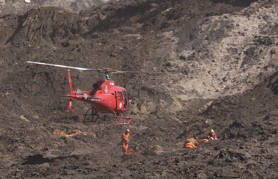 A rescue helicopter prepares to remove a body during a search and recovery effort, days after a dam collapse in Brumadinho, Brazil, Wednesday, Jan. 30, 2019. A torrent of muddy mining waste unleashed by a dam breach that killed at least 84 people in southeastern Brazil is now heading down a small river with high concentrations of iron oxide, threatening to contaminate a much larger river that provides drinking water to communities in five of the country's 26 states. (AP Photo/Andre Penner)
