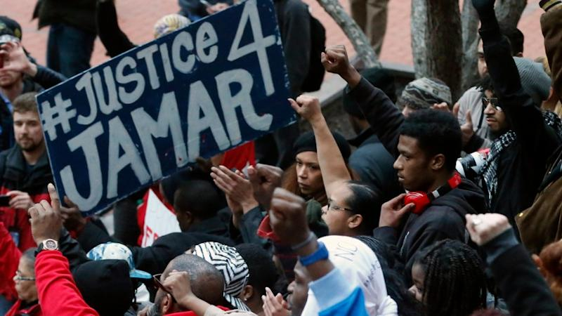 Demonstrators raise their fists during a protest over two Minneapolis police officers fatally shooting Jamar Clark, a black man, in November 2015.