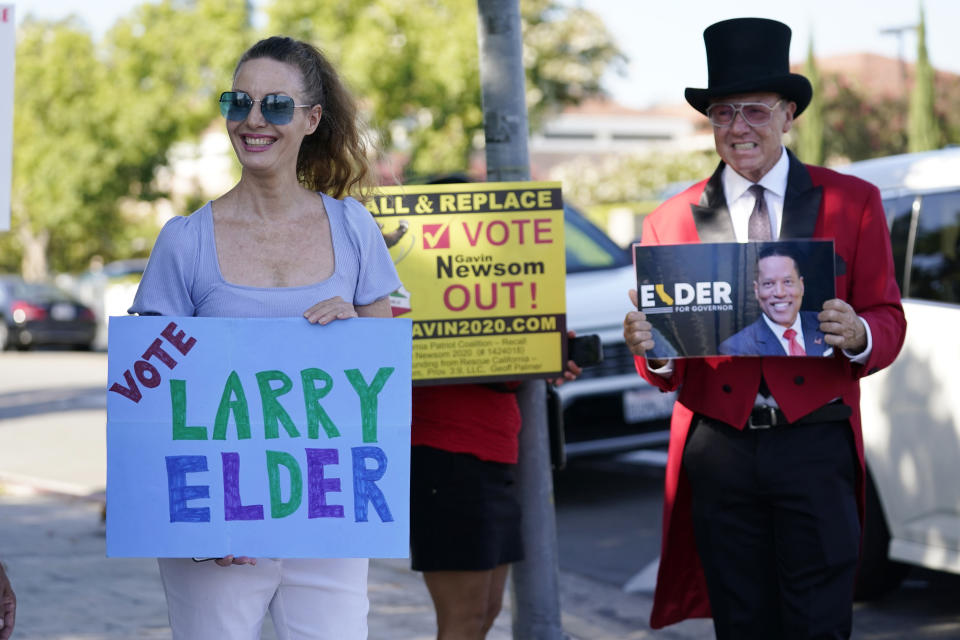 Supporters of the California recall of Gov. Gavin Newsom and Republican candidate Larry Elder hold signs outside of a debate by Republican gubernatorial candidates at the Richard Nixon Presidential Library Wednesday, Aug. 4, 2021, in Yorba Linda, Calif. Newsom faces a Sept. 14 recall election that could remove him from office. (AP Photo/Marcio Jose Sanchez)